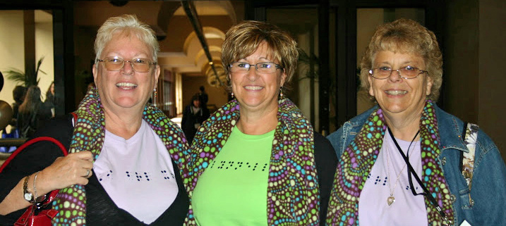 Photo of three members with matching braille shirts