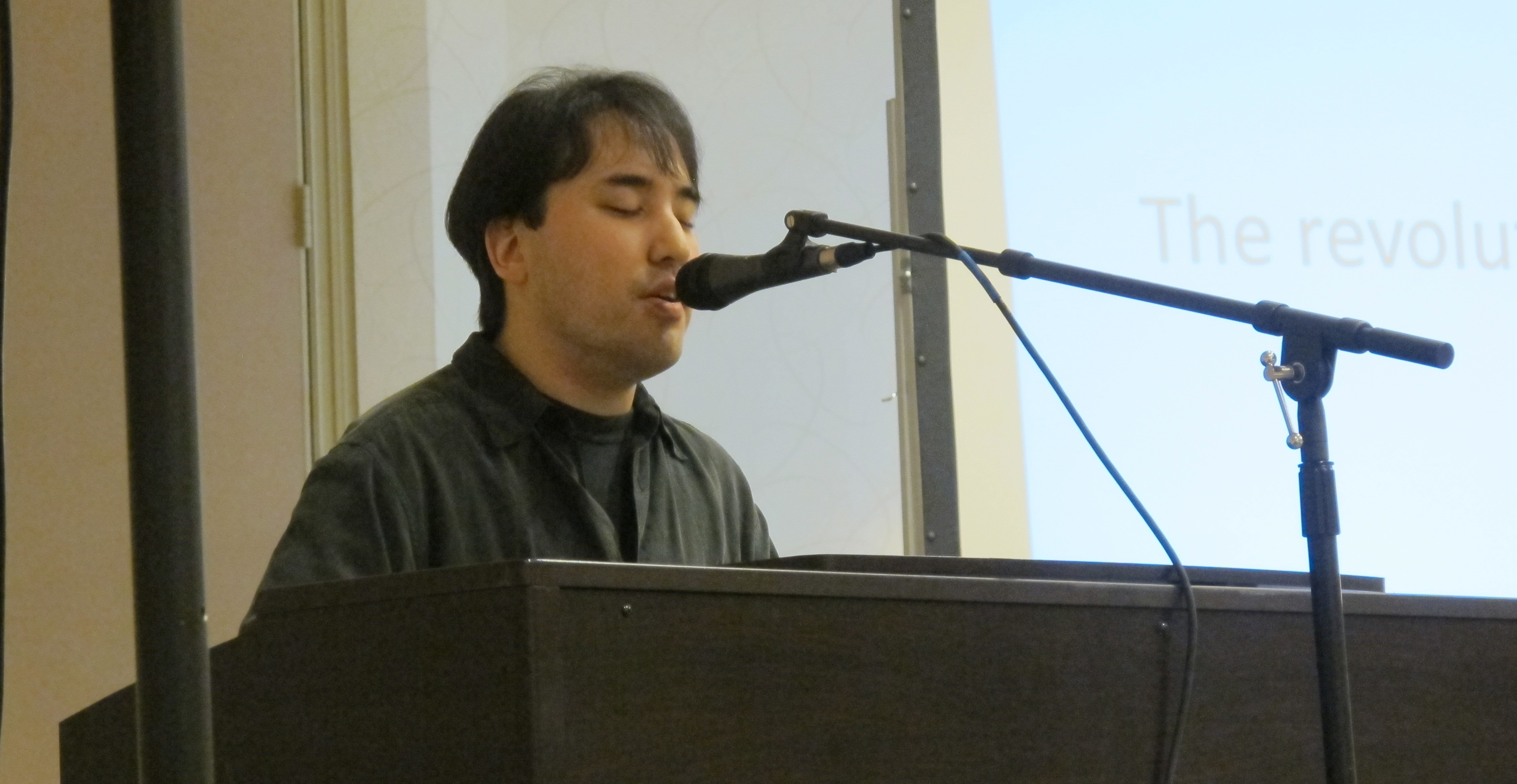 Photo of Ian Oto playing piano and singing